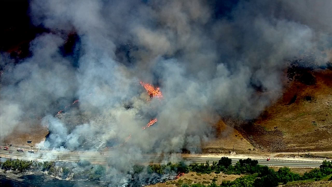 A brush fire burned along State Route 241 near Santiago Canyon Road in Irvine on Monday, July 13, 2015.