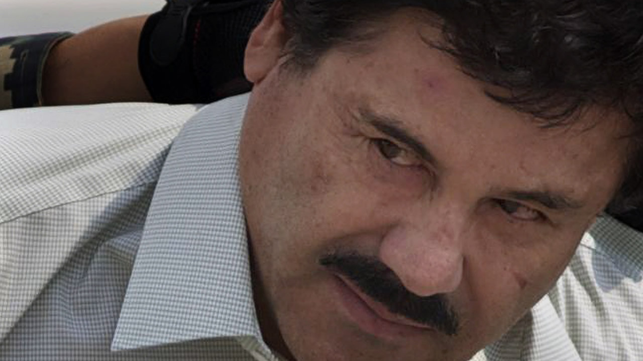 """FILE: Joaquin """"El Chapo"""" Guzman is escorted to a helicopter in handcuffs by Mexican navy marines at a navy hanger in Mexico City, Saturday, Feb. 22, 2014."""