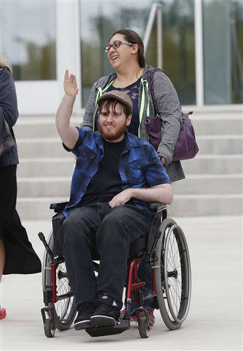 """<div class=""""meta image-caption""""><div class=""""origin-logo origin-image none""""><span>none</span></div><span class=""""caption-text"""">Katie Medley wheels her husband Caleb Medley, who was shot in the face in the 2012 Aurora movie theatre massacre (AP Photo/ Brennan Linsley)</span></div>"""