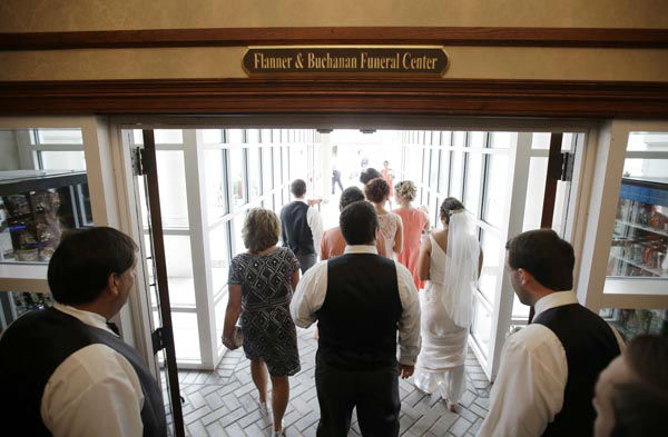 """<div class=""""meta image-caption""""><div class=""""origin-logo origin-image none""""><span>none</span></div><span class=""""caption-text"""">In this June 19, 2015 photo, the wedding party make their way down a hallway towards the open air courtyard where Danessa Molinder and Billy Castrodale are getting married. (AP Photo/ Darron Cummings)</span></div>"""