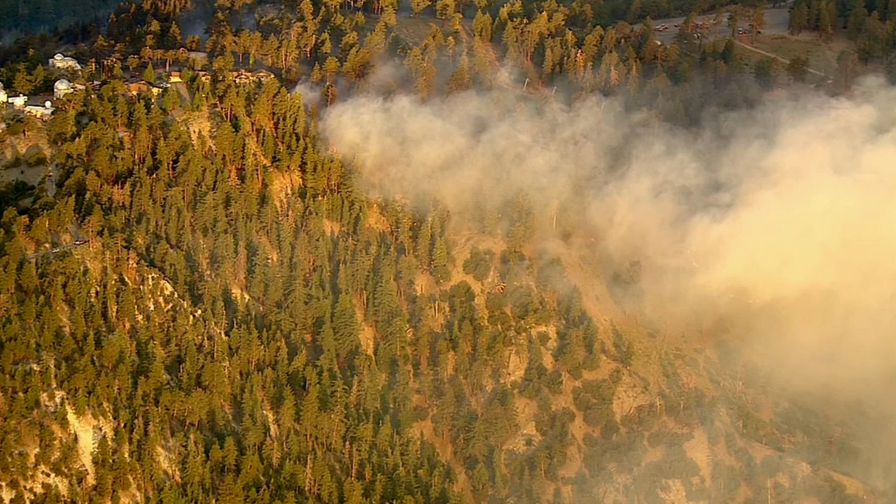 Smoke from the Pine Fire billows above the trees in the Angeles National Forest on Saturday, July 18, 2015.