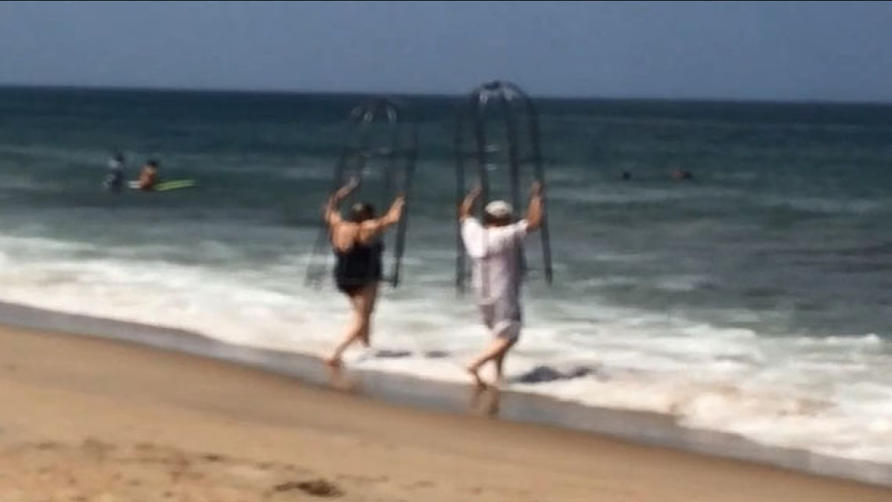 Couple using makeshift shark cages on the Outer Banks