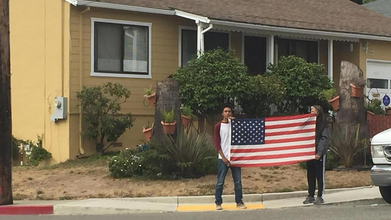 "<div class=""meta image-caption""><div class=""origin-logo origin-image none""><span>none</span></div><span class=""caption-text"">Residents hold an American flag to honor Hayward police Sgt. Scott Lunger, who was shot and killed during an early morning traffic stop in Hayward, Calif. on July 22, 2015. (KGO-TV/Amy Hollyfield)</span></div>"