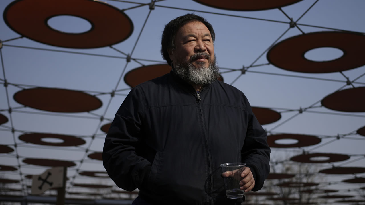 Chinese dissident artist Ai Weiwei walks near a playground outside a shopping mall in Beijing Tuesday, March 24, 2015. (AP Photo/Andy Wong)