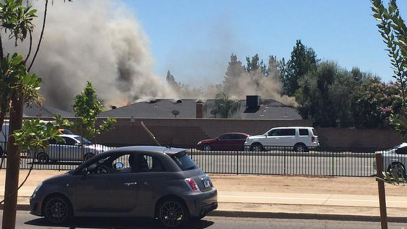 A fire burns at a home on Millbrae Avenue near Palm Avenue in Northwest Fresno on Friday, July 24, 2015.