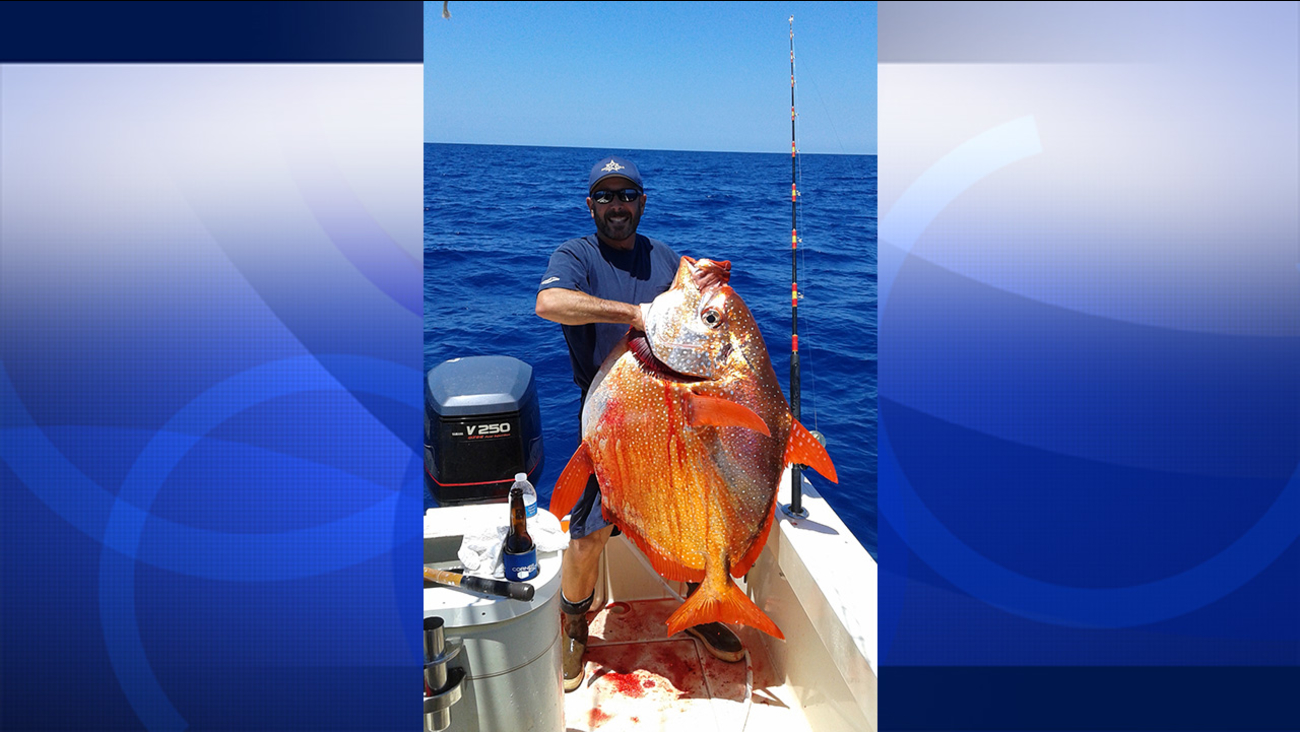 Keith Bridges stands next to the 96-pound opah that he caught in Encinitas on Thursday, July 23, 2015.