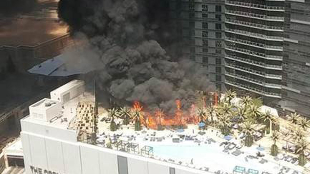 Flames engulf trees and pool cabanas at the Cosmopolitan Hotel of Las Vegas on Saturday, July 25, 2015.