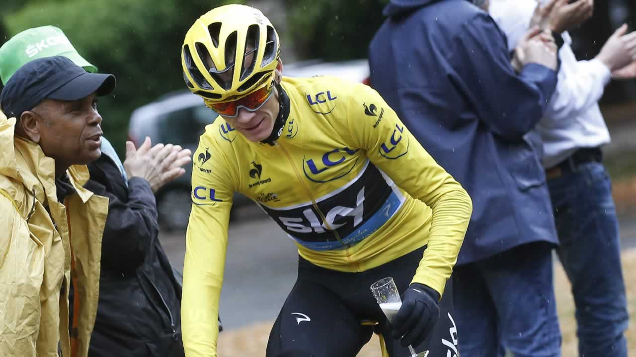 Britain's Chris Froome rides with a glass of champagne after the last stage of the Tour de France cycling race over 109.5 kilometers in Paris, France, Sunday, July 26, 2015.