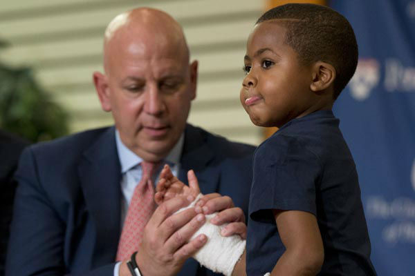 "<div class=""meta image-caption""><div class=""origin-logo origin-image none""><span>none</span></div><span class=""caption-text"">As Dr. L. Scott Levin holds his hand, double-hand transplant recipient eight-year-old Zion Harvey moves his fingers during a news conference Tuesday, July 28, 2015 (AP Photo/ Matt Rourke)</span></div>"