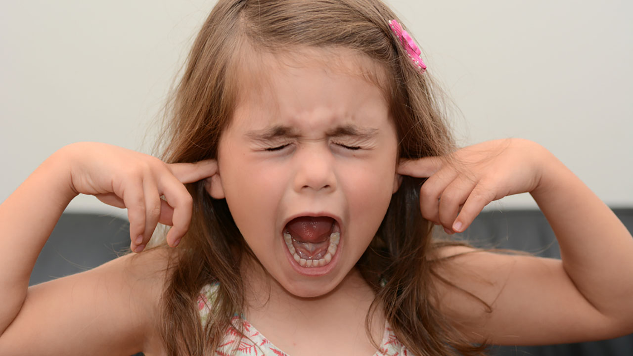 A little girl yelling with her fingers in her ears.