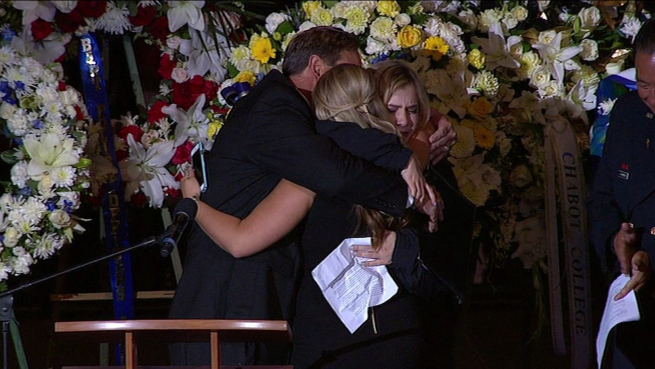 Sergeant Scott Lunger's two daughters and his older brother embrace on stage at his memorial at Oracle Arena in Oakland Calif. on Thursday, July 30, 2015.