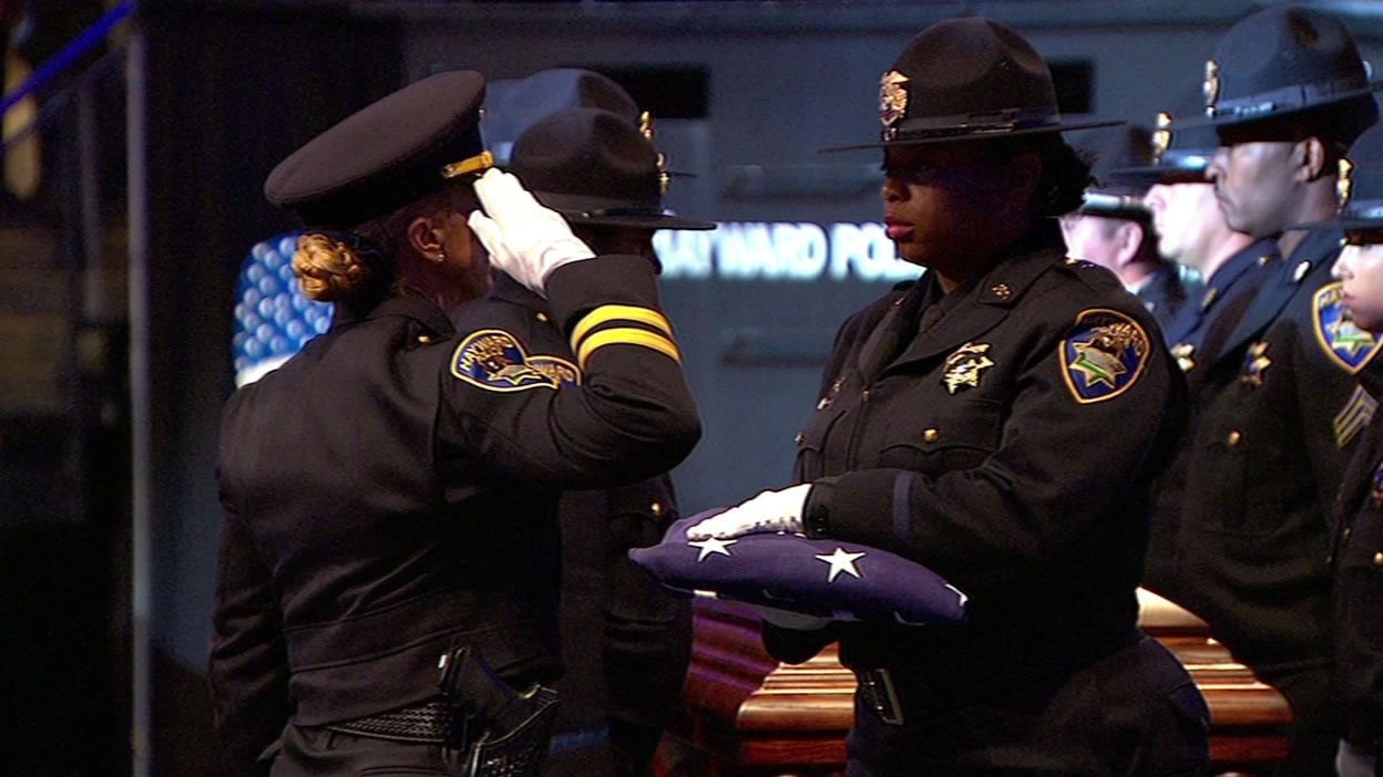 "<div class=""meta image-caption""><div class=""origin-logo origin-image none""><span>none</span></div><span class=""caption-text"">Hayward law enforcement officials prepare the flag to be presented to Sgt. Scott Lunger's family at his memorial at Oracle Arena in Oakland, Calif. on Thursday, July 30, 2015. (KGO-TV)</span></div>"