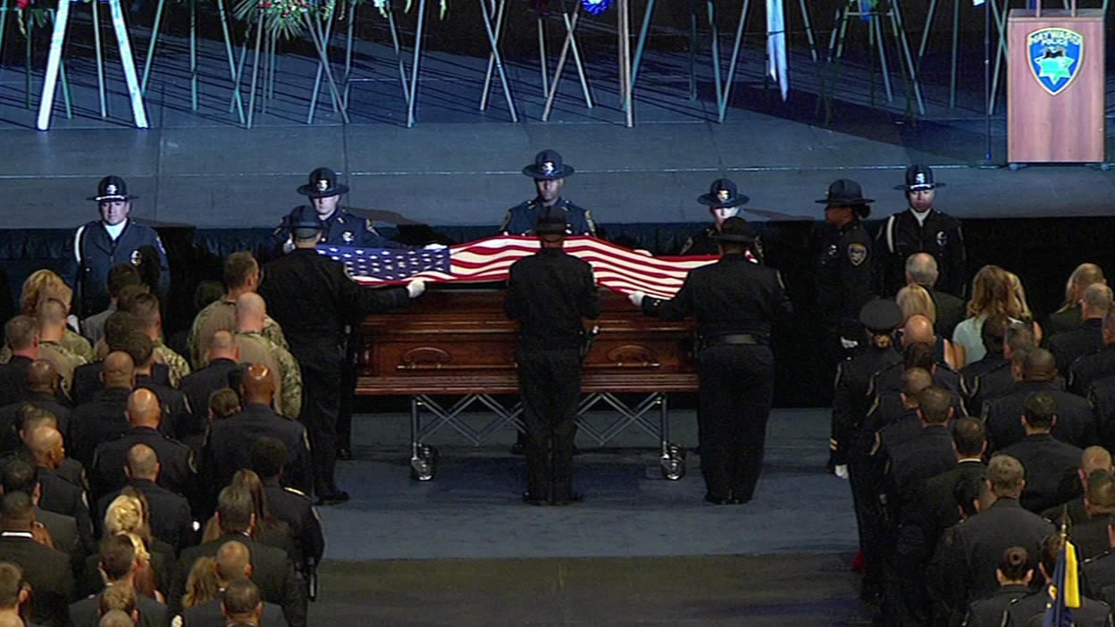 "<div class=""meta image-caption""><div class=""origin-logo origin-image none""><span>none</span></div><span class=""caption-text"">Officers lift the flag from the casket of Sgt. Scott Lunger, which was presented to the Lunger family, at his memorial in Oakland, Calif. on Thursday, July 30, 2015. (KGO-TV)</span></div>"
