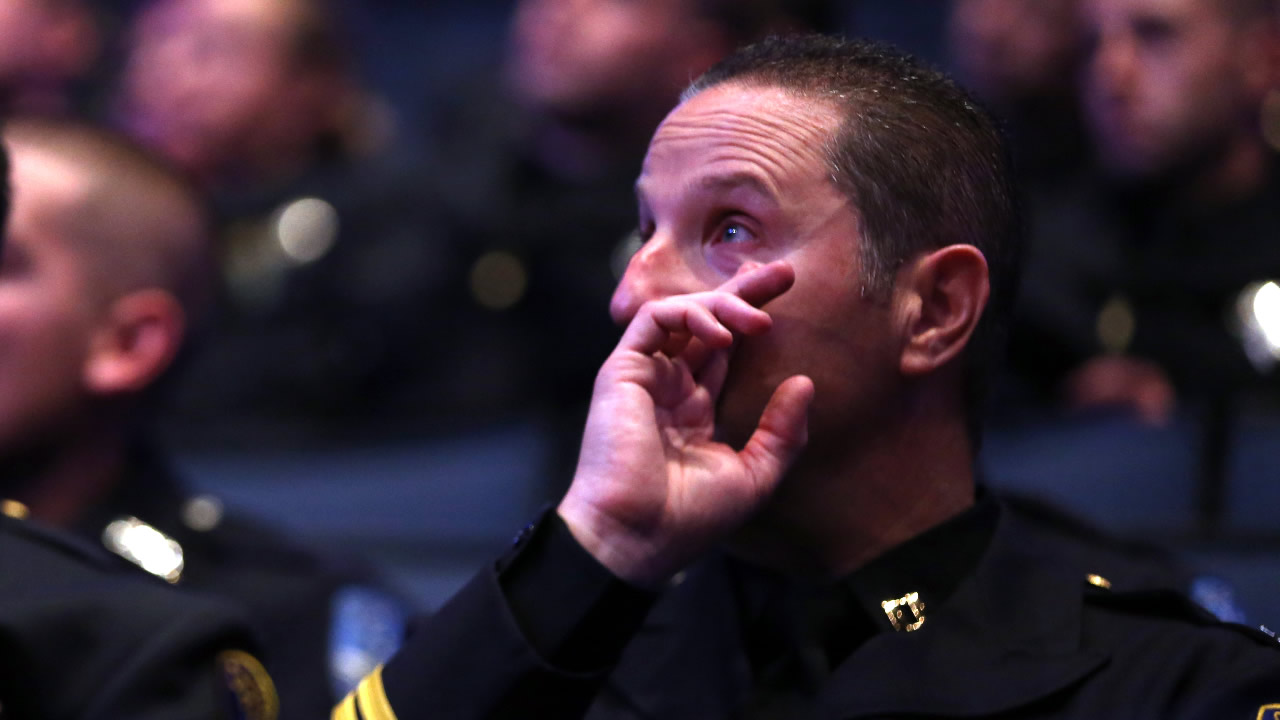 "<div class=""meta image-caption""><div class=""origin-logo origin-image none""><span>none</span></div><span class=""caption-text"">A police officer wipes his eye during a memorial service for Sgt. Scott Lunger at Oracle Arena in Oakland, Calif., Thursday, July 30, 2015. (Ray Chavez/Bay Area News Group via AP)</span></div>"