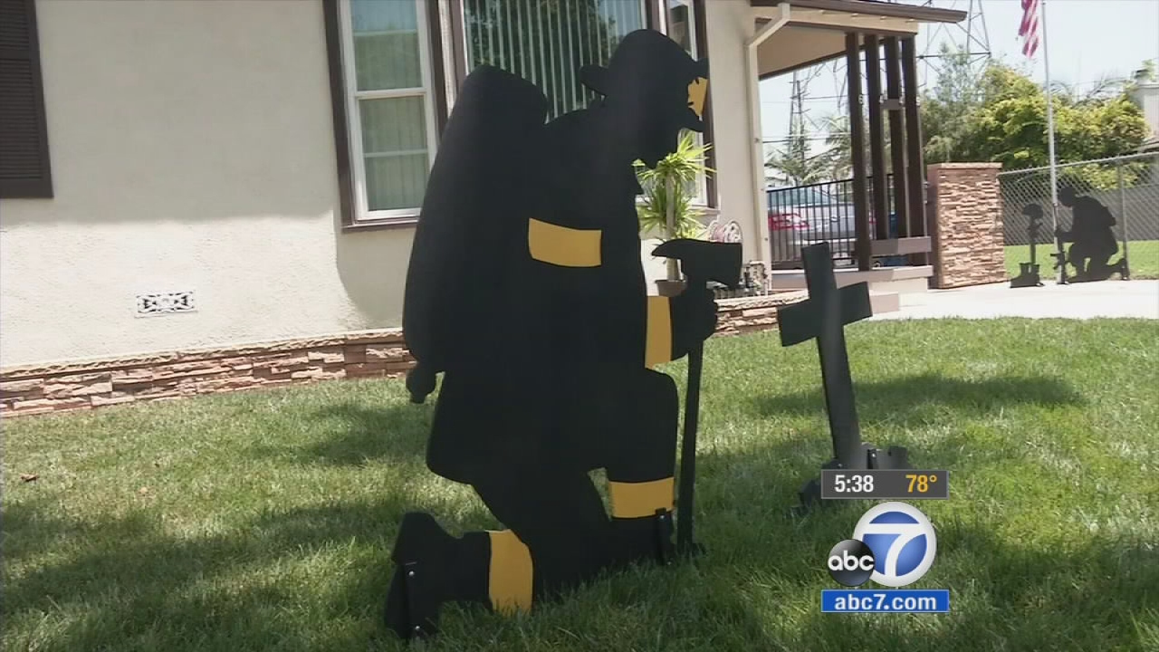 A silhouette of a firefighter, meant as a tribute piece, is put on display on James Krupa's yard.