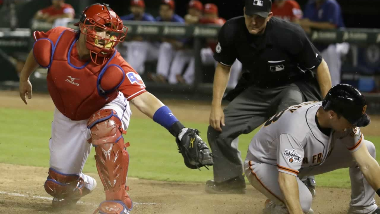 Giants' Buster Posey  slides safely into home plate to score as Texas Rangers catcher Bobby Wilson fields the late throw in Arlington, Texas, Saturday, August 1, 2015.