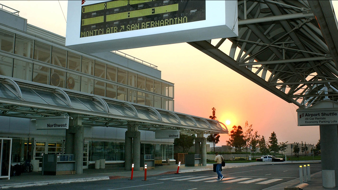 A lone traveler heads towards Ontario International Airport as the sun goes down Sunday, Oct. 26, 2003, in Ontario, Calif.