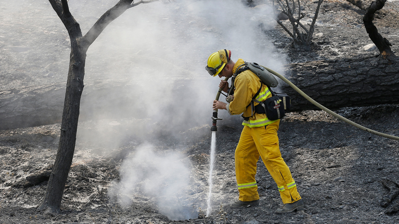 A Sonoma Valley firefighter sprays water on a hot spot from the Rocky fire near Clearlake, Calif., Wednesday, Aug. 5, 2015.