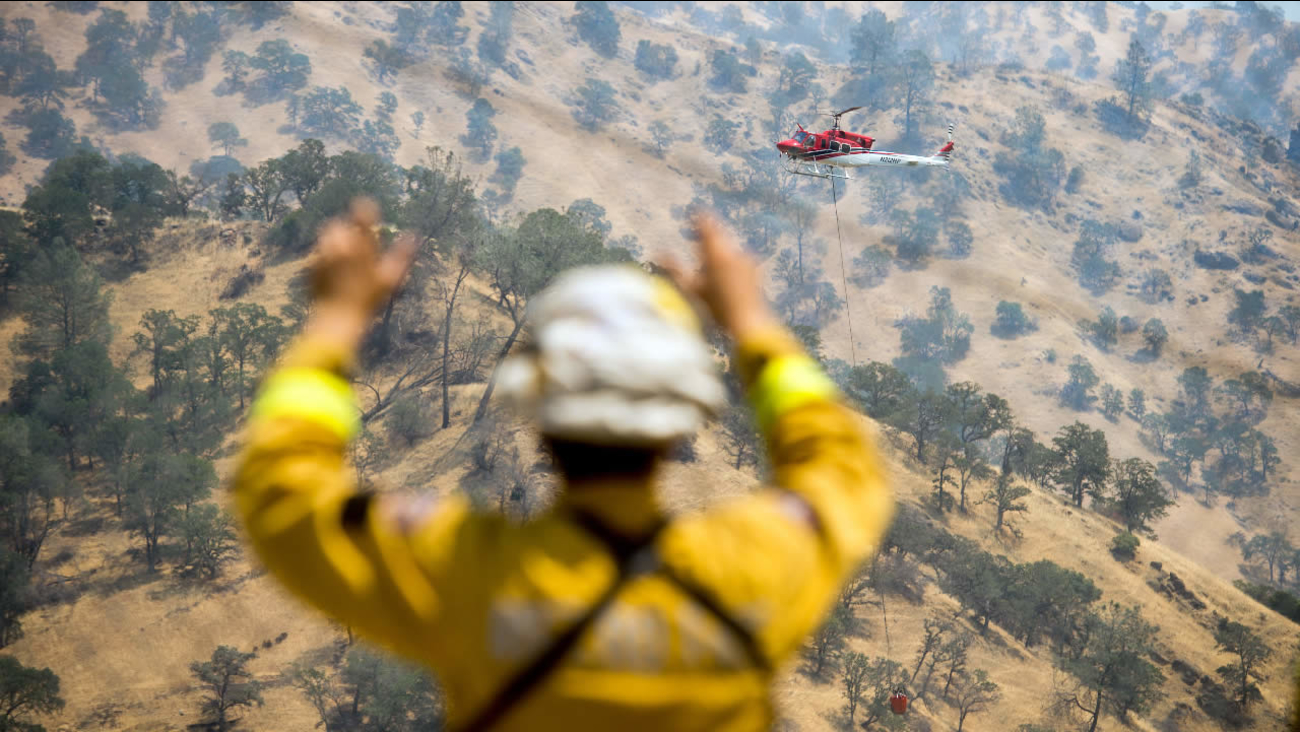 FILE: A firefighter watches a helicopter battle the Wragg fire near Winters, Calif., on Thursday, July 23, 2015.
