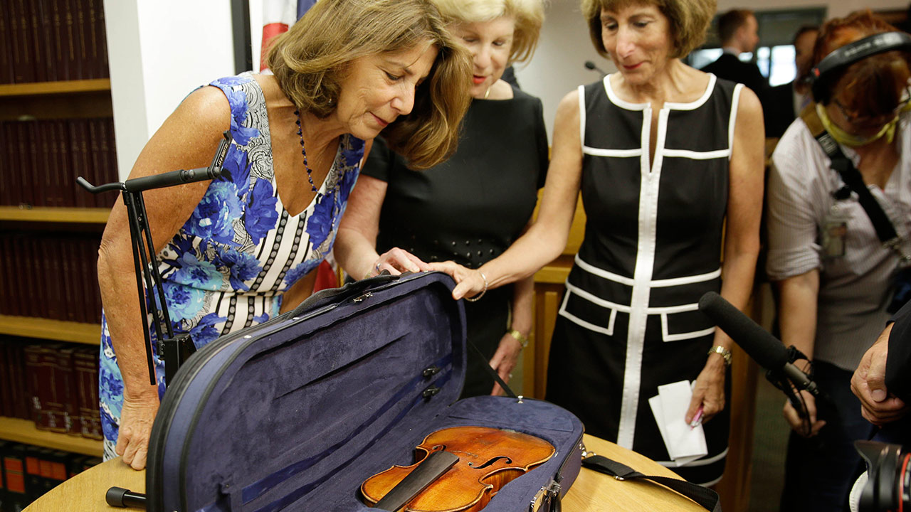 Sisters Amy Totenberg, left, Nina Totenberg, center, and Jill Totenberg get their first look at the Ames Stradivarius violin, Thursday, Aug. 6, 2015, in New York.