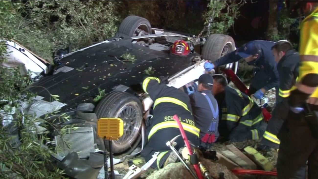Rescuers help extricate two men from their car after they crashed into a tree in Sonoma County, August 8, 2015.