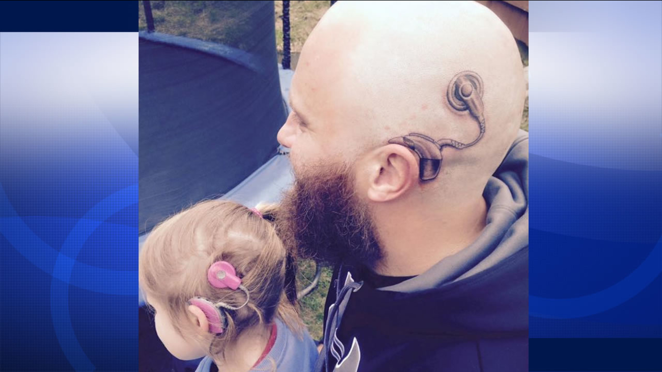 Alistair Campbell shows off the tattoo he got of a cochlear implant that matches his hearing impaired six-year-old daughter's cochlear implant.