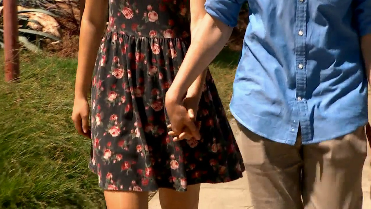 Two teens are shown holding hands while walking through a neighborhood.