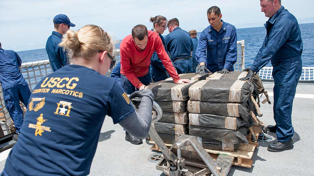 In this July 19, 2015 photo released by the U.S. Coast Guard, Coast Guard Cutter Stratton crew members secure cocaine bales from a self-propelled semi-submersible interdicted in international waters off the coast of Central America.