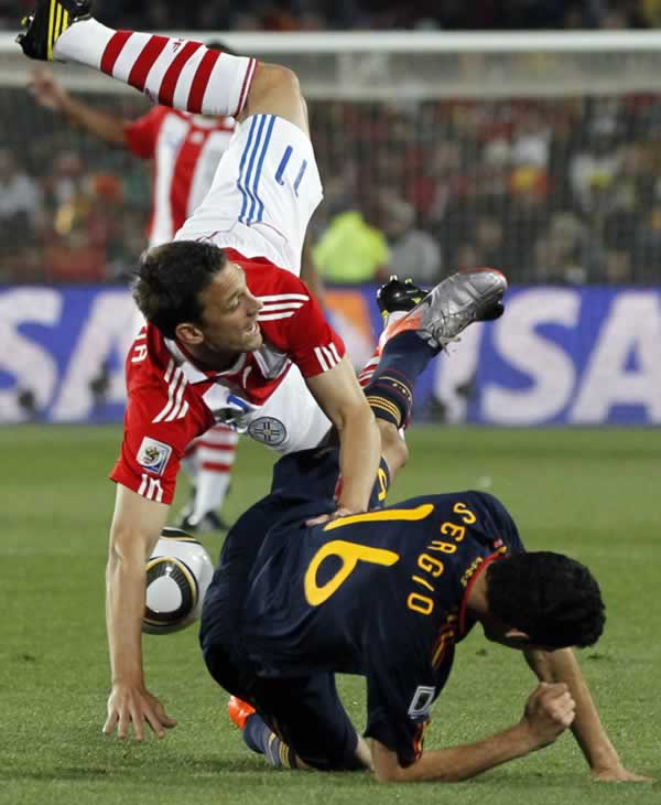 "<div class=""meta image-caption""><div class=""origin-logo origin-image ""><span></span></div><span class=""caption-text"">Paraguay's Jonathan Santana, left, is airborne after a challenge with Spain's Sergio Busquets during the World Cup quarterfinal soccer match between Paraguay and Spain. (AP Photo/Bernat Armague)</span></div>"