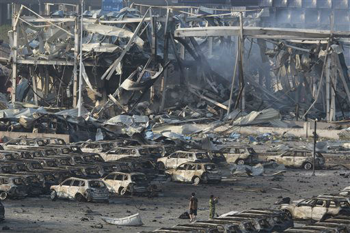 "<div class=""meta image-caption""><div class=""origin-logo origin-image none""><span>none</span></div><span class=""caption-text"">Photographers walk near the charred remains of a warehouse and new cars after an explosion (AP Photo/ Ng Han Guan)</span></div>"