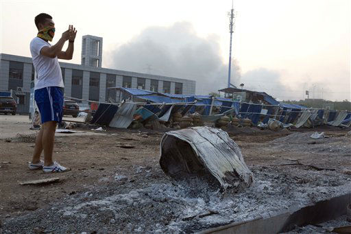 "<div class=""meta image-caption""><div class=""origin-logo origin-image none""><span>none</span></div><span class=""caption-text"">A man takes a photo near a burnt drum that residents said flew from a nearby explosion (AP Photo/ Ng Han Guan)</span></div>"
