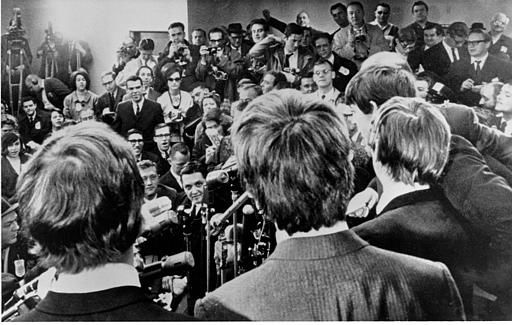 "<div class=""meta image-caption""><div class=""origin-logo origin-image none""><span>none</span></div><span class=""caption-text"">The Beatles face the media on arrival at JFK airport on Feb. 7, 1964. They were also greeted by a screaming crowd estimated at 5,000. (AP Photo)</span></div>"