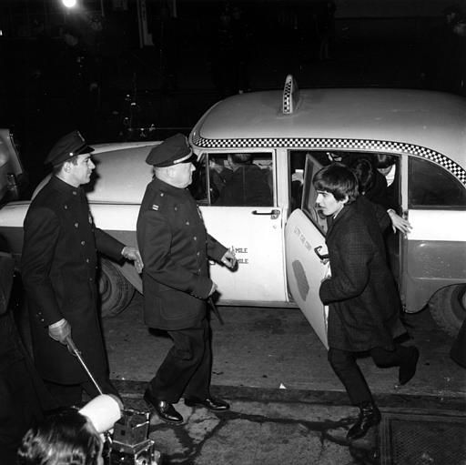 "<div class=""meta image-caption""><div class=""origin-logo origin-image none""><span>none</span></div><span class=""caption-text"">Police security is on hand as guitarist George Harrison leads the way from a taxi-cab to Carnegie Hall's stagedoor on W. 56th St. on Feb. 12, 1964. (AP Photo)</span></div>"