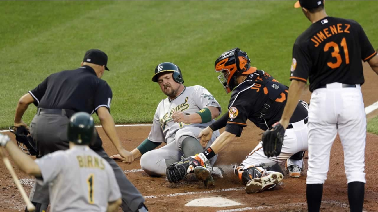 Orioles catcher Caleb Joseph tags out Athletics' Billy Butler on a single by Marcus Semien during the second inning of a baseball game, Friday, Aug. 14, 2015, in Baltimore.