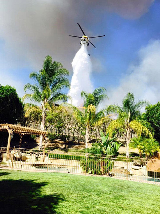 """<div class=""""meta image-caption""""><div class=""""origin-logo origin-image none""""><span>none</span></div><span class=""""caption-text"""">ABC7 viewer Jeannetta Purdue-Rizkalla took a photo of a helicopter dropping water on the Rustic Fire right behind her Simi Valley home on Friday, Aug. 14, 2015. (Jeannetta Purdue-Rizkalla)</span></div>"""