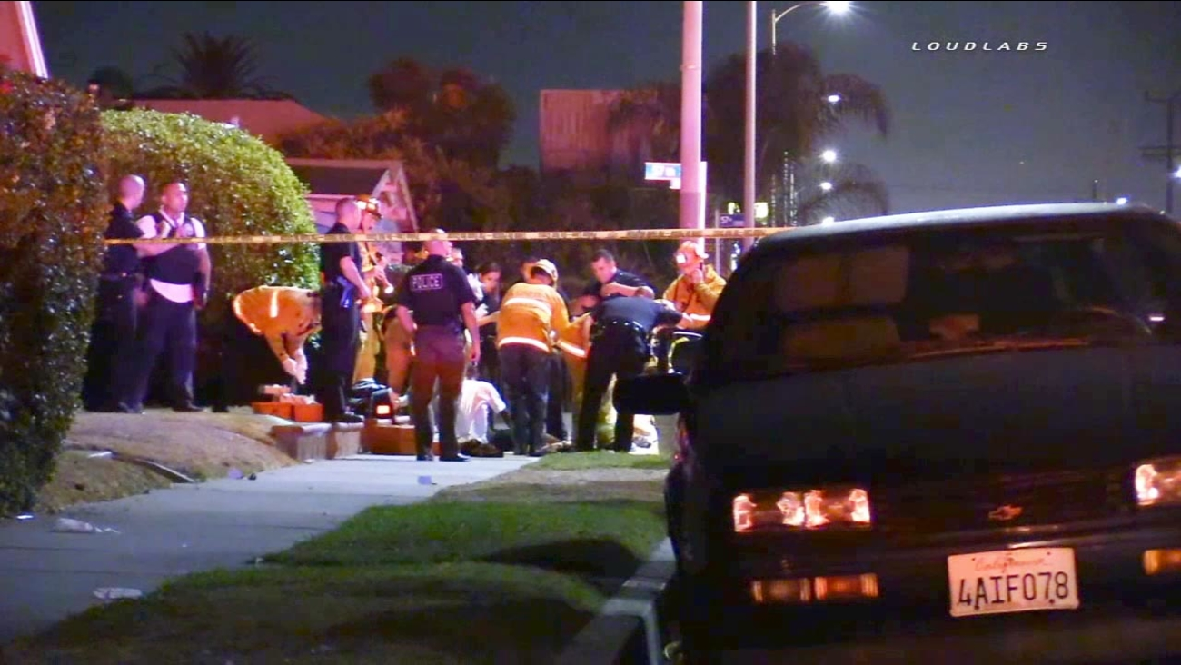Emergency personnel are shown at the scene of a shooting at 57th Street and South Normandie Avenue in South Los Angeles on Saturday, Aug. 15, 2015.