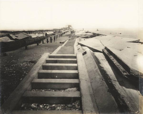 "<div class=""meta image-caption""><div class=""origin-logo origin-image none""><span>none</span></div><span class=""caption-text"">View of causeway toward the arched bridge, wrecked by the hurricane. (Special Collections, University of Houston Libraries)</span></div>"
