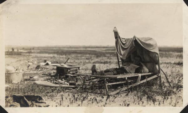 "<div class=""meta image-caption""><div class=""origin-logo origin-image none""><span>none</span></div><span class=""caption-text"">A man lies in a cot, surrounded by the debris from his former home. (Special Collections, University of Houston Libraries)</span></div>"