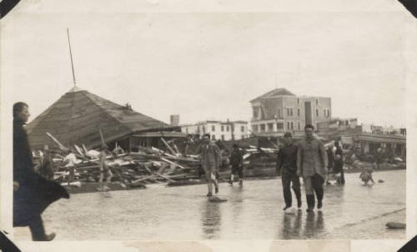 "<div class=""meta image-caption""><div class=""origin-logo origin-image none""><span>none</span></div><span class=""caption-text"">Wreckage from Murdoch's Bathhouse in the background while pedestrians walk along Seawall Boulevard after the hurricane. (Special Collections, University of Houston Libraries)</span></div>"