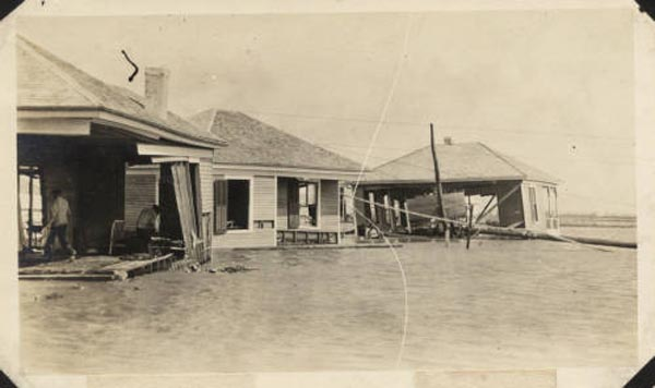 "<div class=""meta image-caption""><div class=""origin-logo origin-image none""><span>none</span></div><span class=""caption-text"">Wrecked houses submerged in sand on the east end of Galveston on Seawall Boulevard. People can be seen inside the ruin of one of the houses, presumably salvaging belongings. (Photo/Special Collections, University of Houston Libraries)</span></div>"