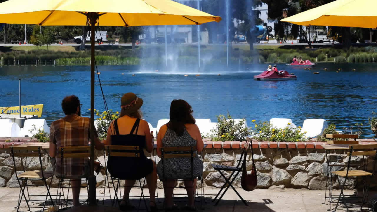 FILE: Visitors to Echo Park Lake near downtown Los Angeles shade themselves under an umbrella as paddle boats keep close to a large fountain to keep cool on Friday, Aug. 14, 2015.