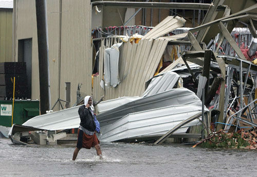 "<div class=""meta image-caption""><div class=""origin-logo origin-image none""><span>none</span></div><span class=""caption-text"">James Smith wades past a storm damaged building after Hurricane Katrina struck the Gulf Coast Monday,  Aug. 29, 2005 in Gulfport, Miss.. (Photo/JOHN BAZEMORE)</span></div>"