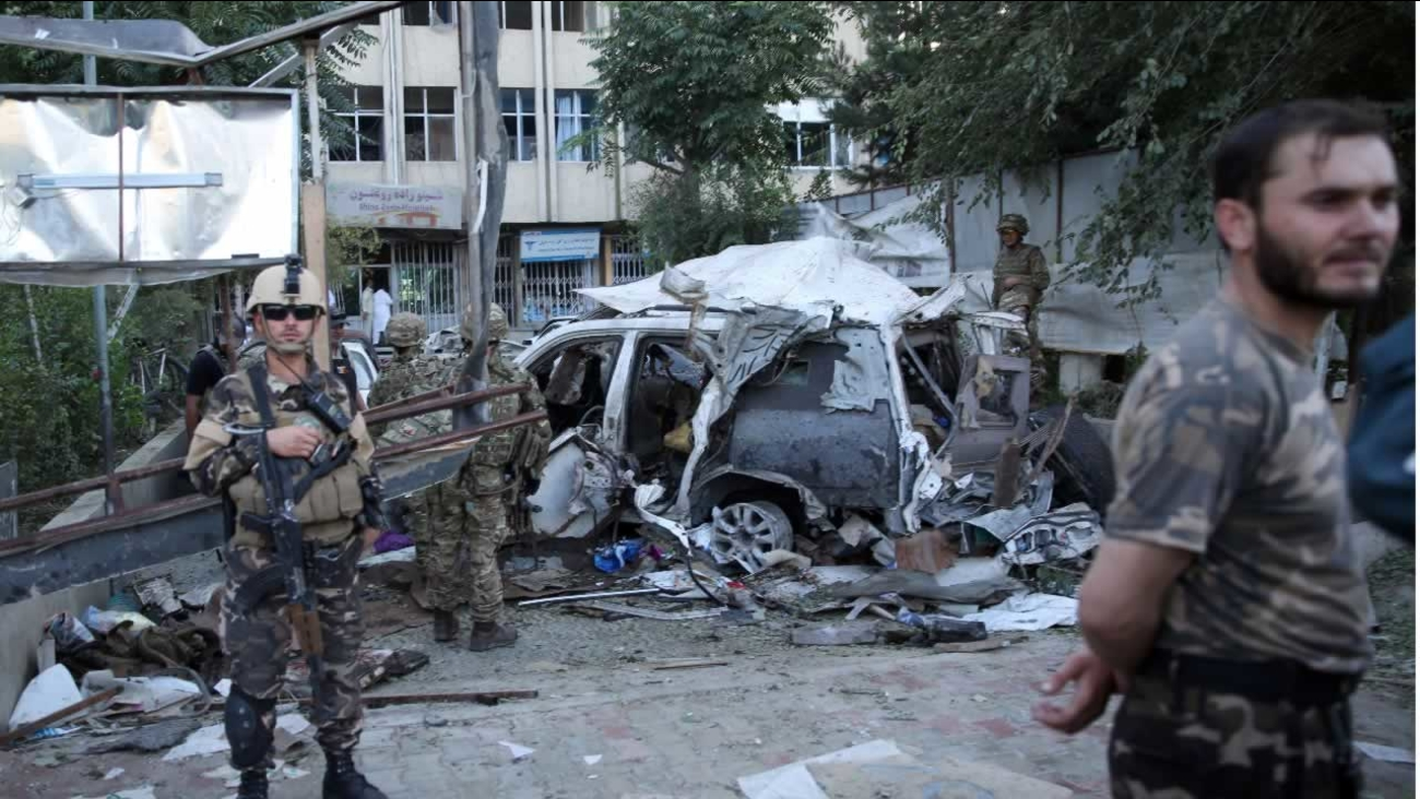 Afghan security forces and British soldiers inspect the site of a suicide attack in the heart of Kabul, Afghanistan, Saturday, Aug. 22, 2015.