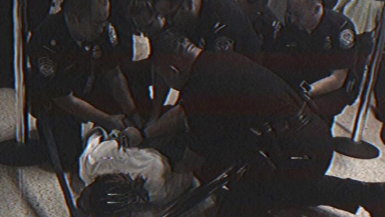Wiz Khalifa is shown on the ground as LAX Airport Customs officers hold him down and handcuff him on Saturday, Aug. 22, 2015.