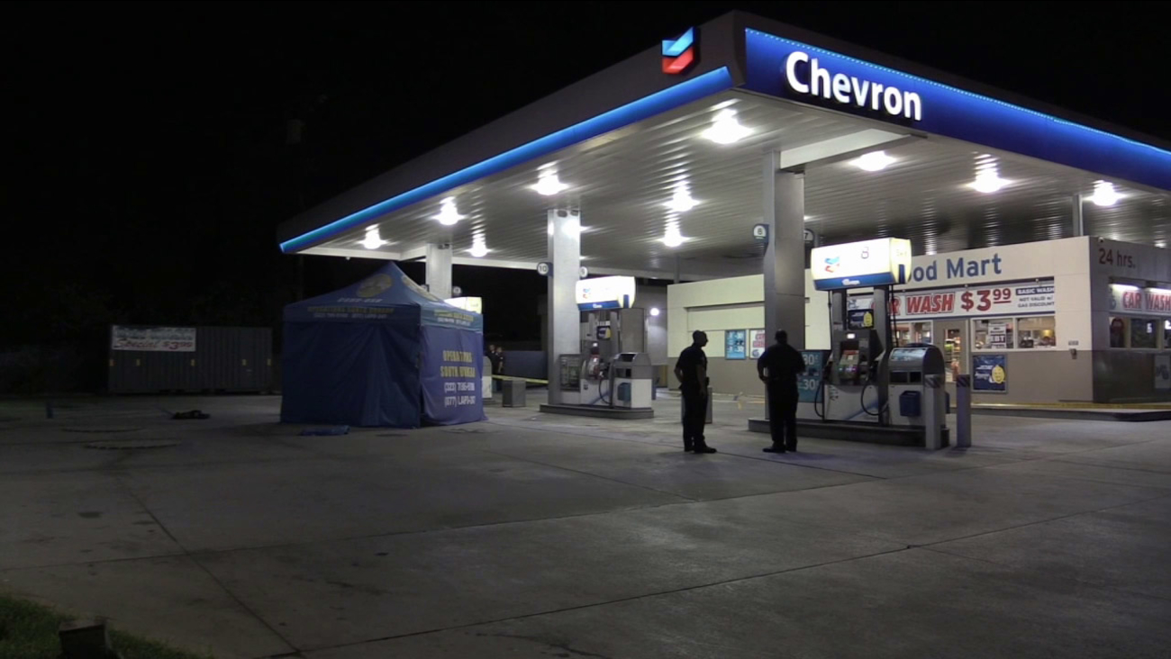 Investigators are shown at a Chevron gas station at Florence Avenue and Flower Street in South Los Angeles following a fatal shooting on the 110 Freeway on Sunday, Aug. 23, 2015.