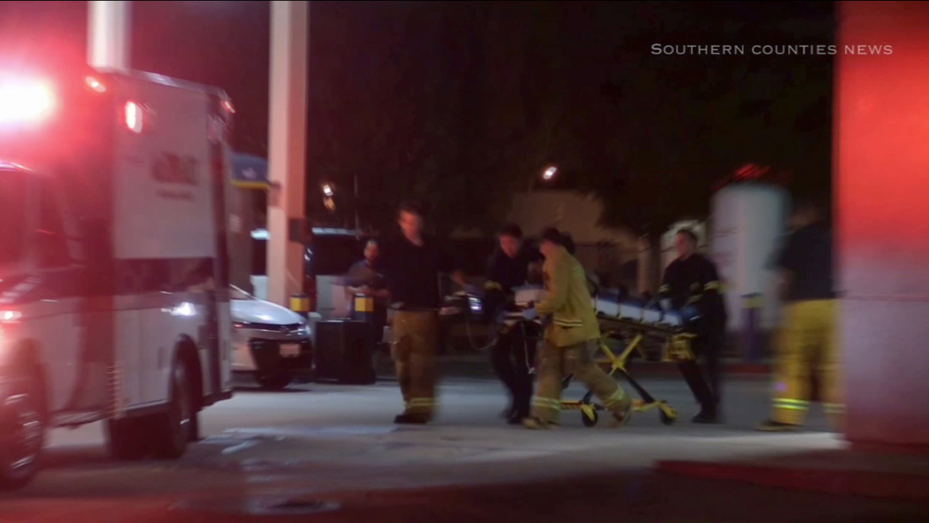 Emergency responders move a victim shot inside a Valero gas station in Carson into an ambulance on Tuesday, Aug. 25, 2015.