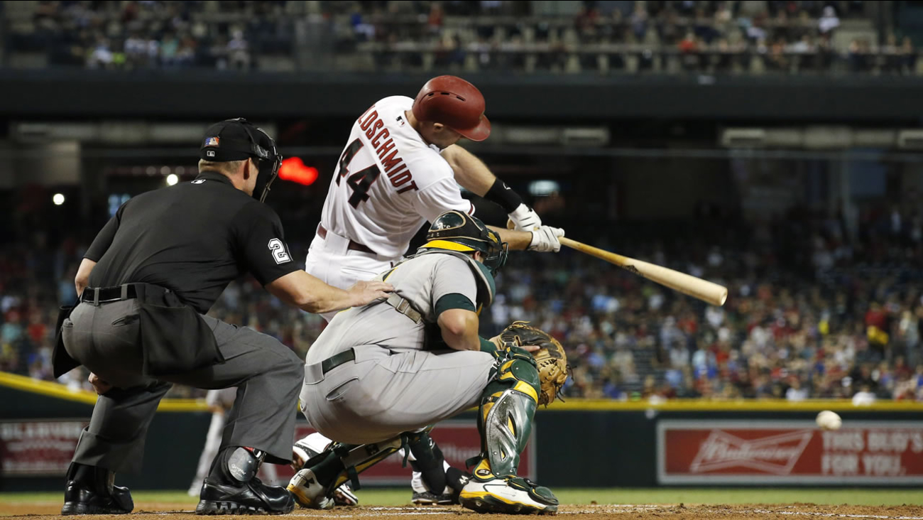 Arizona Diamondbacks' Paul Goldschmidt (44) hits an infield grounder as Oakland Athletics' Stephen Vogt watch during a baseball game Friday, Aug. 28, 2015, in Phoenix.