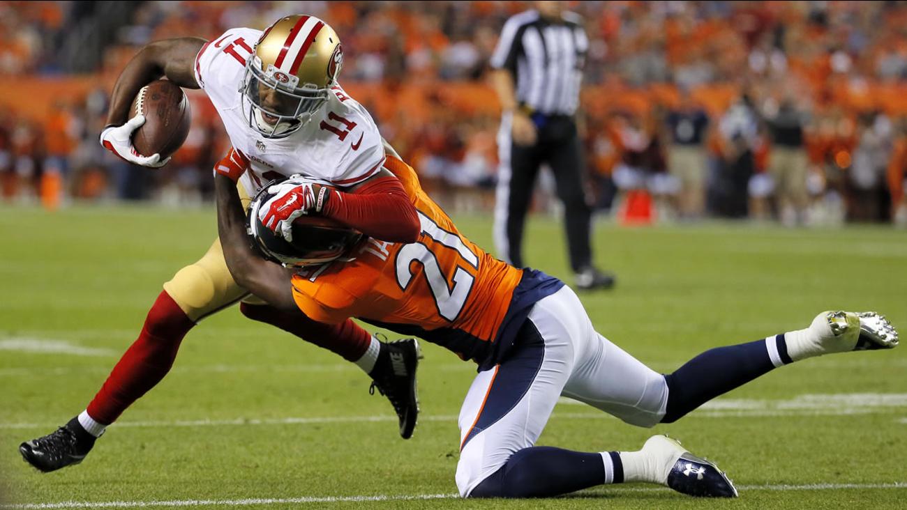 San Francisco 49ers wide receiver Quinton Patton (11) is hit by Denver Broncos cornerback Aqib Talib (21) during an NFL preseason football game, Saturday, Aug. 29, 2016, in Denver.