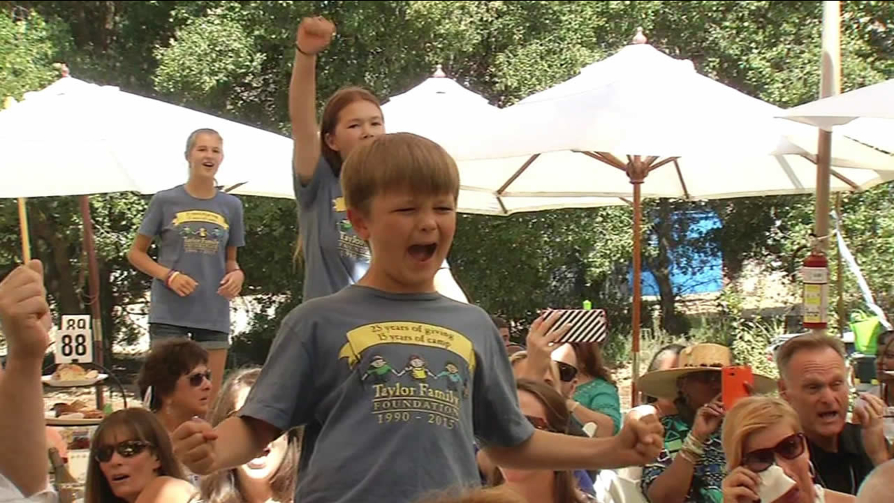 "A boy sings along to Journey's ""Don't Stop Believing"" during The Taylor Family Foundation's ""Day in the Park"" fundraiser in Livermore, Calif. on Sunday, August 30, 2015."