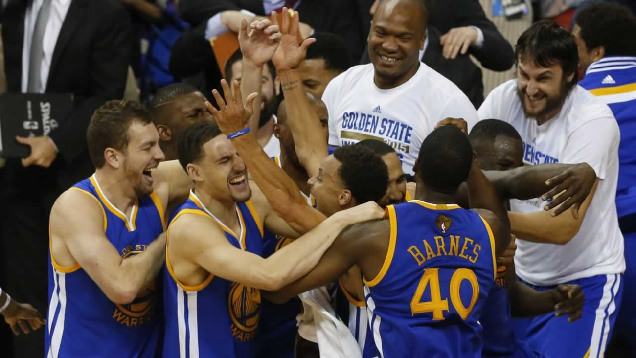 Golden State Warriors players celebrate after Game 6 of basketball's NBA Finals against the Cleveland Cavaliers in Cleveland, Tuesday, June 16, 2015.